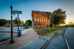 Spoorwegsporen en gebouwen bij zonsondergang, in Greensboro van de binnenstad, stock foto's