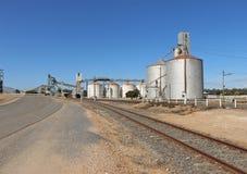 Spoorwegsporen en tarwesilo's tegen een heldere blauwe hemel Stock Foto's