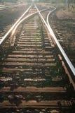 Spoorwegsporen met balk en grint tegen zonneschijn Stock Foto