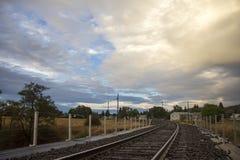 Spoorwegsporen met mening van wolken stock fotografie