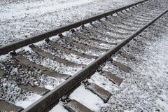 Spoorwegsporen met sneeuw worden behandeld die royalty-vrije stock afbeeldingen