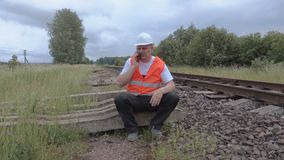 Spoorwegzitting dichtbij spoorweg en het spreken op telefoon stock videobeelden