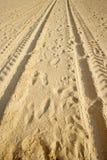 Sporen op een zandig strand stock afbeelding