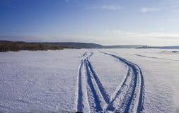 Sporen op het rivierijs van een sneeuwscooter stock foto's