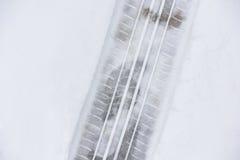 Sporen van een auto op witte duidelijke sneeuw stock foto