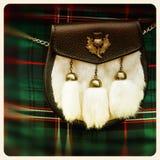 Sporran old photo. Traditional Scottish sporran over tartan background. Retro style photo Royalty Free Stock Photo