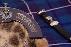 Sporran & sgian dubh. Close up of a Sporran with a sgian dubh blurred on a tartan background Royalty Free Stock Image