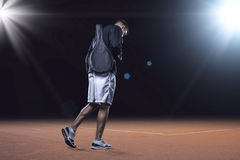 Sporstman going to the clay tennis playground. Tennis player walking by the clay tennis court carrying a racket in cover, evening time royalty free stock image