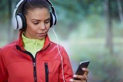 Sporstwoman choosing songs for jogging Royalty Free Stock Photos