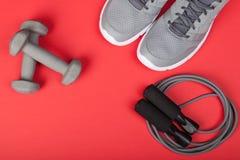 Sportów buty dumbbells i omijać arkana na czerwonym tle, Odgórny widok Sprawność fizyczna, sport i zdrowy stylu życia pojęcie, Zdjęcia Stock