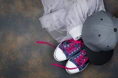 Sportów buty, szyfon spódnica i baseball nakrętka na podłoga, zdjęcia stock