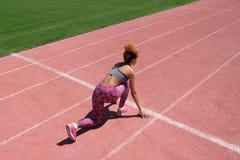 Sportövningar och sträckning eller förbereda av en löpare att starta på stadion En ung härlig mörkhyad flicka i en grå behållare royaltyfria foton