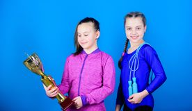 Sport achievement. Girls athletic kids celebrate victory. Athletic girls with golden goblet. Win championship. Our team. First place. Children gymnasts athletic stock photo