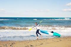 Sport acquatico di estate Uomo atletico bello con l'ente sexy che tiene il kajak trasparente della canoa fotografia stock libera da diritti