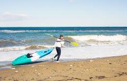 Sport acquatico di estate Uomo atletico bello con l'ente sexy che tiene il kajak trasparente della canoa immagine stock libera da diritti