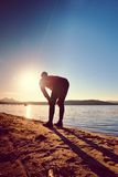 Sport active man running and exercising on the beach at sunset. Royalty Free Stock Photos