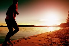 Sport active man running and exercising on the beach at sunset. Stock Photography