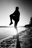 Sport active man running and exercising on the beach at sunset. Royalty Free Stock Photography