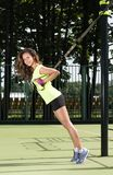 Sport activities outdoors. Exercises with straps. Beautiful young woman in athletic shape. Street Playground in the background Royalty Free Stock Photography