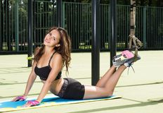 Sport activities outdoors. Exercises with straps. Beautiful young woman in sportswear lying on the rug. Street in the background area Stock Photography