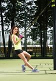 Sport activities outdoors. Exercises with TRX. Beautiful young woman in athletic shape. Street Playground in the background Royalty Free Stock Photos