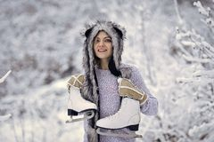 Sport, activity, health. Happy woman smile with figure skates at trees in snow. Vacation, holidays, hobby, lifestyle. Girl with skating shoes in winter clothes royalty free stock images