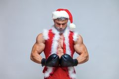 Sport, activity. Santa Claus with boxing glove. Young muscu. Lar man wearing Santa Claus hat demonstrate his muscles. on a homogeneous gray background stock photography