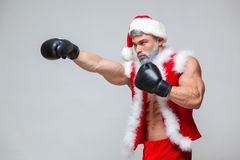 Sport, activity. Sexy Santa Claus with boxing glove. Young muscular man wearing Santa Claus hat demonstrate his muscles. On a homogeneous gray background Stock Photos