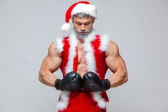 Sport, activity. Sexy Santa Claus with boxing glove. Young muscular man wearing Santa Claus hat demonstrate his muscles. On a homogeneous gray background Stock Images