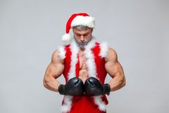 Sport, activity. Sexy Santa Claus with boxing glove. Young muscular man wearing Santa Claus hat demonstrate his muscles Stock Images