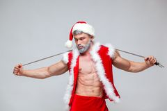 Sport, activity. Santa Claus with skipping rope. Young muscular man wearing Santa Claus hat demonstrate his muscles Royalty Free Stock Images