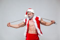 Sport, activity. Sexy Santa Claus with skipping rope. Young muscular man wearing Santa Claus hat demonstrate his muscles. On a homogeneous gray background Royalty Free Stock Image