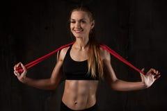 Sport aktivitet Gullig kvinna med överhopprepet Muskulös flicka bl arkivbild