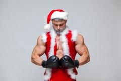 Sport aktivitet Sexiga Santa Claus med boxninghandsken Den unga muskulösa mannen som bär den Santa Claus hatten, visar hans muskl Arkivbilder
