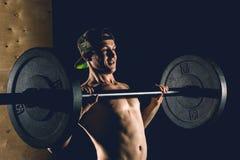 Sport, allenamento Ritratto del primo piano di un allenamento muscolare dell'uomo con il bilanciere alla palestra Immagine Stock Libera da Diritti