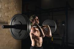 Sport, allenamento Ritratto del primo piano di un allenamento muscolare dell'uomo con il bilanciere alla palestra Fotografia Stock