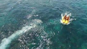 Sport aquatique moteur de touristes de bateau de banane, avec le fond de ciel bleu banque de vidéos