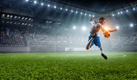 Soccer player at stadium. Mixed media. Sport arena and soccer player hitting ball. Mixed media Royalty Free Stock Image