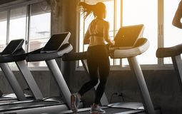 Sport asian woman running on treadmills doing cardio training,Cross fit body and muscular in the gym,Toned image,Back views stock photo