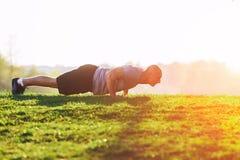 sport Atleta che fa spinta-UPS al tramonto nel parco Esercitazione muscolare e forte del tipo Fotografie Stock