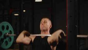 Sport aufgeblähter Mann führt die anhebenden Gewichte durch, die stehende Übung für die Muskeln der Schultern durchführen stock video footage