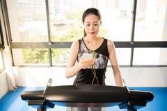 Sport Aziatische vrouw het lopen smartphone die van het tredmolengebruik mus luistert Stock Foto