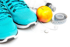 Sport background. Blue running shoes  and apple with objects isolated on white background Stock Photo