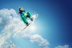 Sport background. Snowboarder jumping. Snowboarder jumping against blue sky Stock Photo
