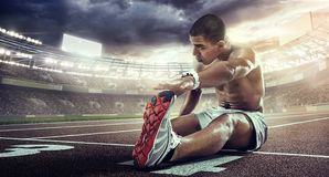 Sport backgrounds. Runner stretching on the the start line. Dramatic view stock image