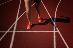 Sport backgrounds. Sprinter starting on the running track. Dramatic image. Red running track with female runner stock image