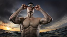 Sport backgrounds. Young athletic swimmer standing near the sunset river. stock photo