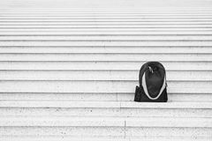 Sport bag on stairs. Traveling and vacation. Black backpack outdoor. Success and loneliness. Beauty and fashion, copy space Stock Images