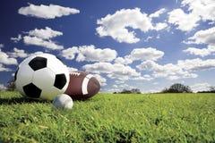 Sport balls. Soccer,baseball and football on green grass under a beautiful sky Vector Illustration