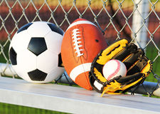 Sport balls. Soccer ball, american football and baseball. In yellow glove. Outdoors Royalty Free Stock Photos